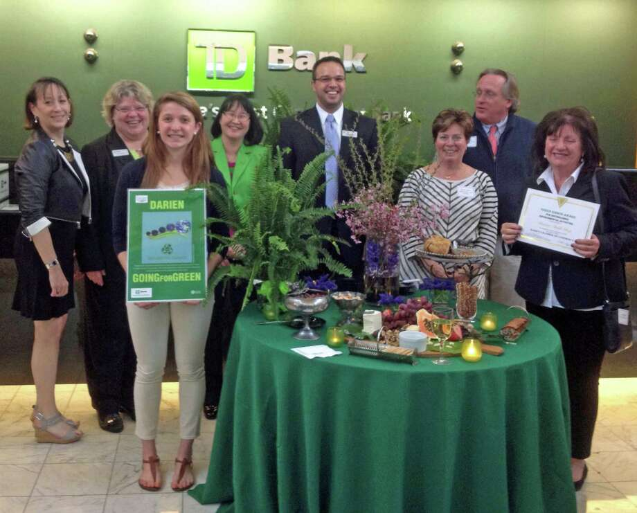 At the recent Darien Chamber of Commerce Going for Green awards event were, from left, Carol Wilder-Tamme, of the chamber; Paula Csengo, Darien branch manager of TD Bank; Amanda Bieler, runner-up in the poster contest; Kim Karl, TD Bank relationship manager; Gianni Dimeglio, TD Bank private client relationship manager; Dorine Bosler, Darien High School graphics arts instructor; Al Tibbetts, Tibbetts, Keating & Butler LLC and chairman of the chamber board; Carol Smith, award winner for the Darien Thrift Shop. Photo: Contributed Photo, Contributed / Darien News