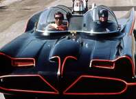 Burt Ward, US actor, and Adam West, US actor, both in costume as the 'Dynamic Duo' riding in the Batmobile in a publicity still issued for the television series, 'Batman', USA, circa 1966. The television series featuring DC Comics characters, starred West as 'Batman', and Ward as 'Robin'.