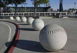 Baseball sculptures line the curb across from Lot A, near AT&T Park in San Francisco, Calif. on Tuesday, April 29, 2014. The Giants are proposing to build a large mixed-use community on the site, but the plans may be derailed if Prop. B, which would impose height limits on waterfront developments, is passed by voters.