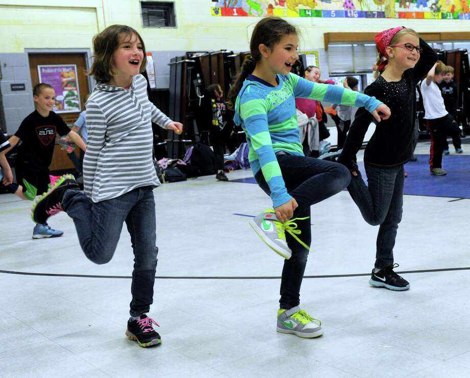 """From left, Jeannette Zeichik, Sophia Chnowski and Brooklyn Snyder are among the kids participating Tuesday morning, April 29, 2014, in Huckleberry Hill's  """"Rise and Shine Morning Boost"""" exercise program. Photo: Carol Kaliff / The News-Times"""