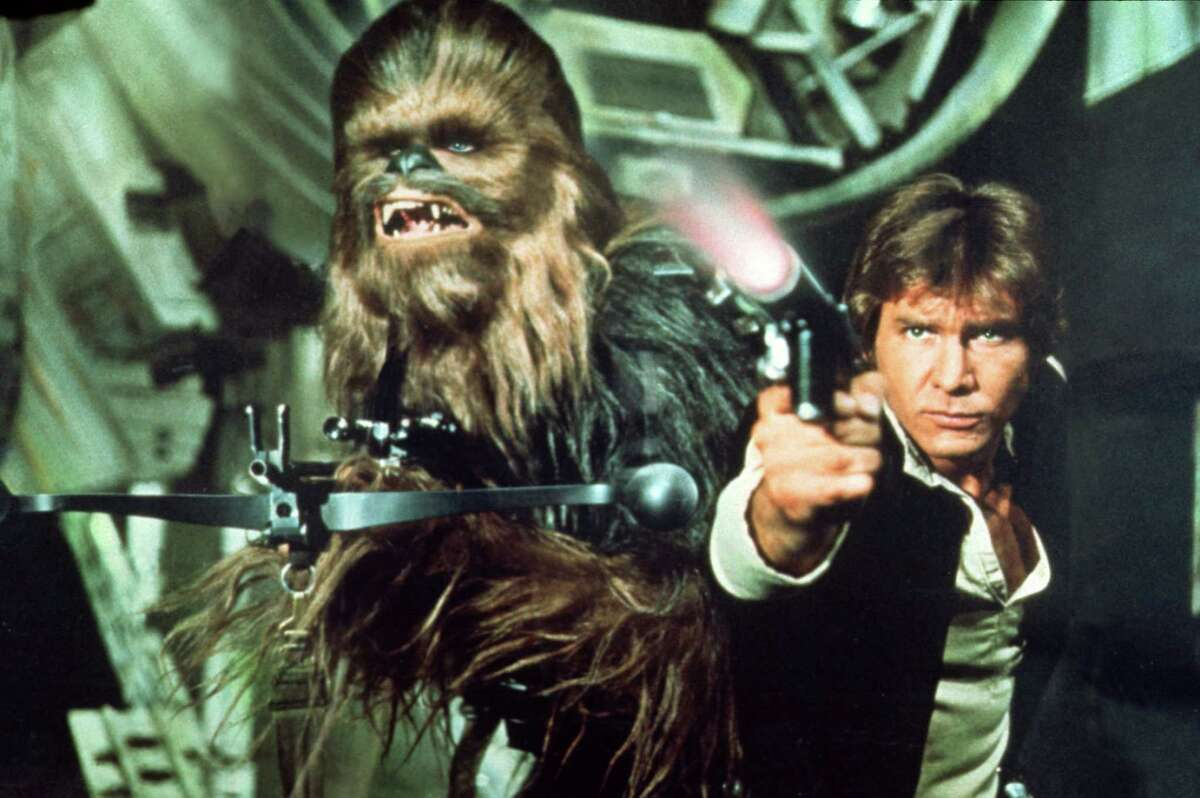 STAR WARS Trilogy. Lucas film Ltd. & TM.-- PICTURED: Peter Mayhew as Chewbacca and Harrison Ford as Han Solo. HOUCHRON CAPTION (09/21/2004) SECSTAR COLORFRONT: THE STARS: From far left, C-3PO (Anthony Daniels),(Not in picture) Princess Leia (Carrie Fisher), (Not in picture) Luke Skywalker (Mark Hamill), Yoda (Frank Oz), (Not in picture) Chewbacca (Peter Mayhew) and Han Solo (Harrison Ford) are part of the Star Wars trilogy's makeover for DVD. HOUCHRON CAPTION (05/18/2005) SECSTAR COLOR: FAVE HALF-WITTED, SCRUFFY-LOOKING NERF-HERDER HAN SOLO: The ultimate bad-boy hot-rodder transported to space in a souped-up Falcon. He's the Fonz to Luke's Richie Cunningham. HOUCHRON CAPTION (05/18/2005) SECSTAR COLOR: MANS BEST FRIEND CHEWBACCA: As cuddly as a kitten, as loyal as a puppy, as strong as a bull and as homely as a gorilla. But give us a can of shag-carpet cleaner and we'll keep him. We just wonder why he bothers with stupid humans.