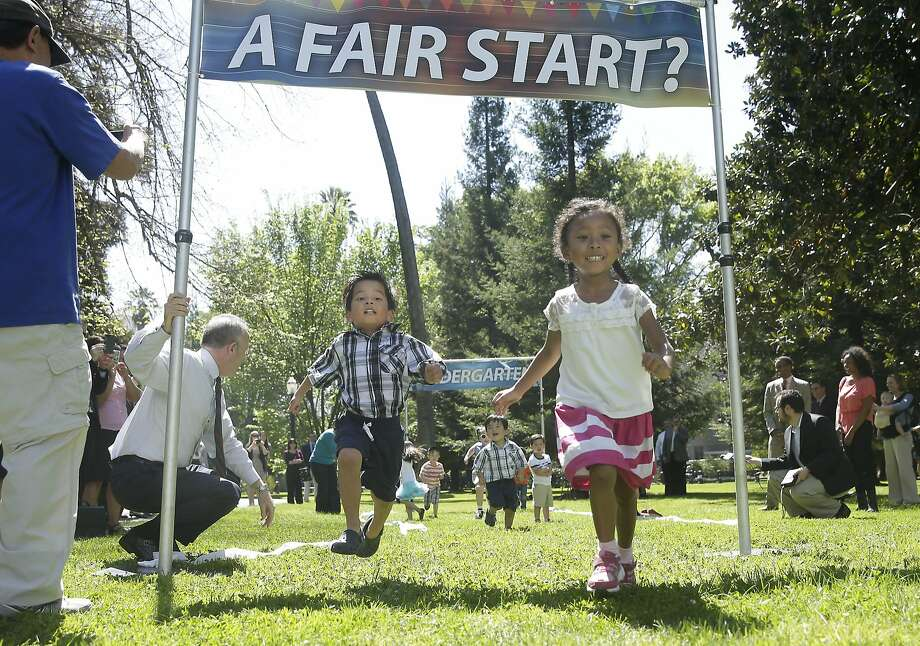 "Madison Williams, 4, right, crosses the finish line ahead of Aiden Ha, 5, left, during a mock race among a group of preschool children Wednesday, April 8, 2014, a the Capitol in Sacramento, Calif.  The race was held to promote the proposed legislation for Universal Pre-Kindergarten and Preschool  authored by Senate President Pro Tem Darrell Steinberg, D-Sacramento, kneeling at left and Sen. Carol Liu, D-La Canada Flintridge, not pictured.  Supporters of the ""Kindergarten Readiness Act,"" say the bills would strengthen early language development and give low-income children a better start entering their first year of school.   (AP Photo/Rich Pedroncelli) Photo: Rich Pedroncelli, Associated Press"