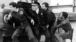 Steve Guttenberg, George Gaynes, Andrew Rubin and Michael Winslow pursue a criminal in a scene from the film 'Police Academy', 1984.