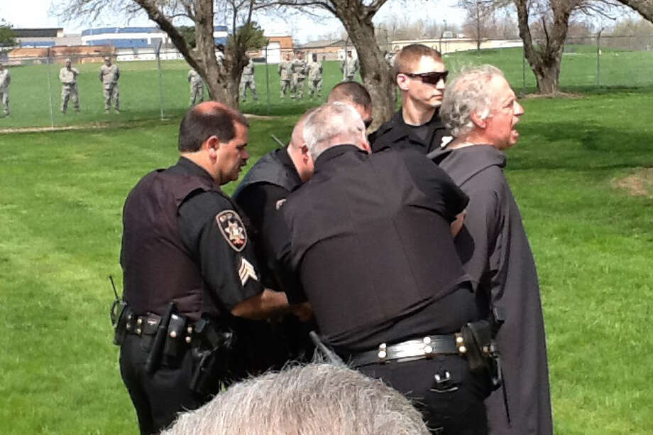 Protester John Amidon is placed under arrest on April 28, 2012, at Hancock Field, a New York National Guard airbase outside Syracuse that operates unmanned MQ-9 Reapers. (Provided)