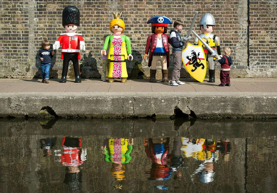 Toys come alive:Children fence with a life-size knight and play with other Playmobil characters on the canalside at Camden in north London. The toy company is celebrating its 40th anniversary. Photo: Leon Neal, AFP/Getty Images