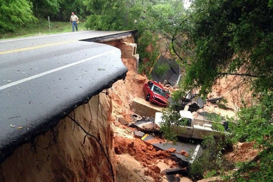 End of the road: A car and a pickup sit in the bottom of a ravine after a section of the Scenic Highway collapsed near 