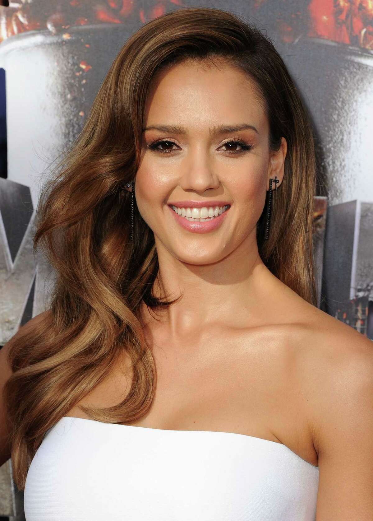 """Jessica Alba Voluminous curls starting at the chin complement Jessica's oval face shape and strapless top. """"For big waves, use either heated Velcro rollers or a large-barrel curling iron,"""" instructs Hill. """"Rollers will give more volume, so they work well on finer hair. Curling irons are better for thicker hair as they help smooth each section. Whatever method you choose, remember that the bigger the section, the looser the wave will be."""" Read: 4 sunglasses shapes that never go out of style"""