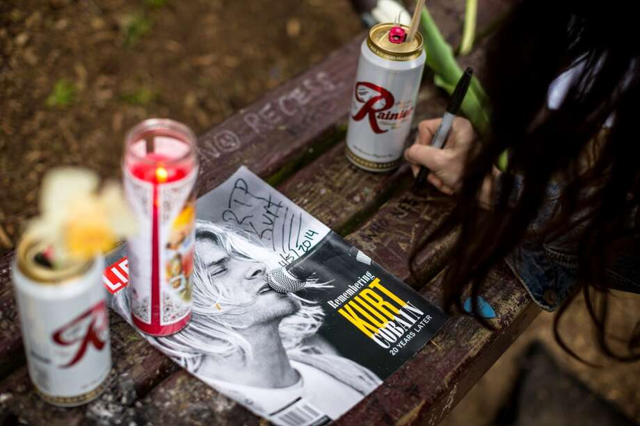 "Portland resident Kim Hoffman scrawls the quote, ""who needs action when you have words?"" in memory of Nirvana's lead singer, Kurt Cobain, on a bench near the home where he died on the 20th anniversary of his death Saturday, April 5, 2014, at Viretta Park in Seattle, Wash. Photo: Jordan Stead, AP"