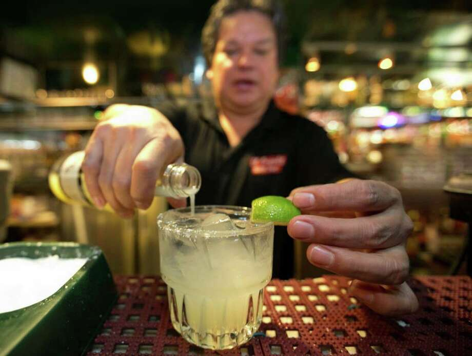 In this Monday, April 28, 2014 photo, bartender Mario Sanchez crafts a margarita cocktail at the bar of El Coyote, a Mexican restaurant in Los Angeles. Thousands of restaurateurs from coast to coast who have fallen victim to the Great Green Citrus Crisis of 2014. The lime has skyrocketed in price in recent weeks, quadrupling or, in some areas, going even higher. (AP Photo) ORG XMIT: MER2014043009290002 / AP