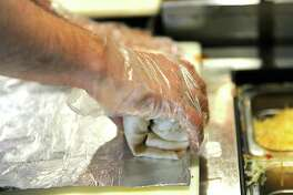 Brian Parks makes a burrito at Bombers Burrito Bar on Lark St. Monday, April 28, 2014 in Albany, N.Y  (Lori Van Buren / Times Union)