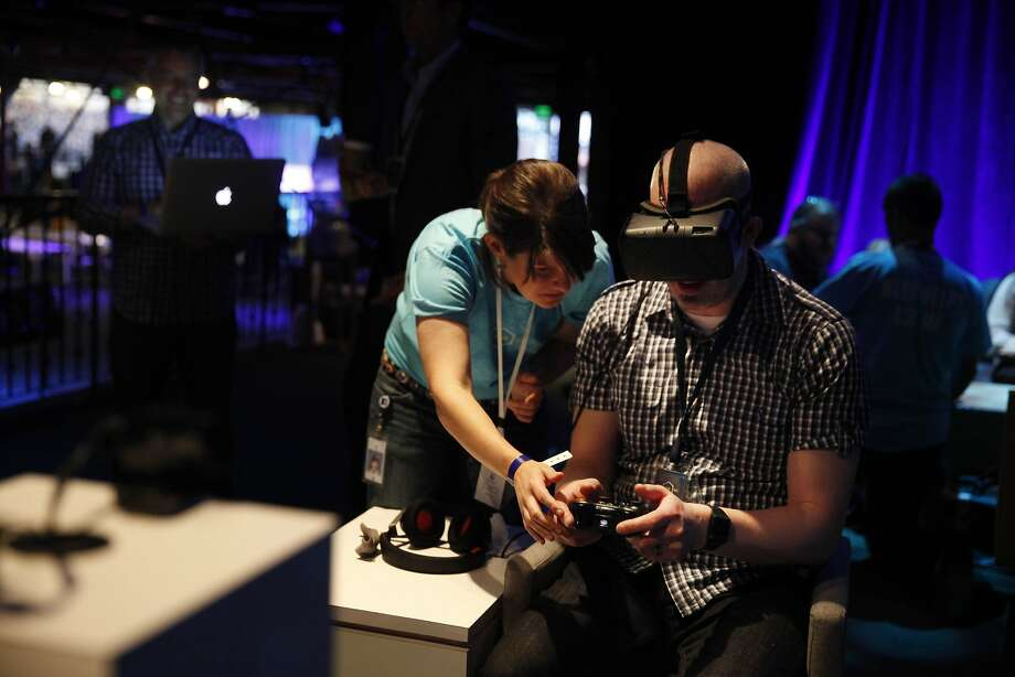 AJ Glasser, Facebook strategic partner development, left, games partnership assists Mike Bjerkness, 8thBridge director of engineering as he tries out Oculus VR's virtual reality platform. Photo: Lea Suzuki, The Chronicle
