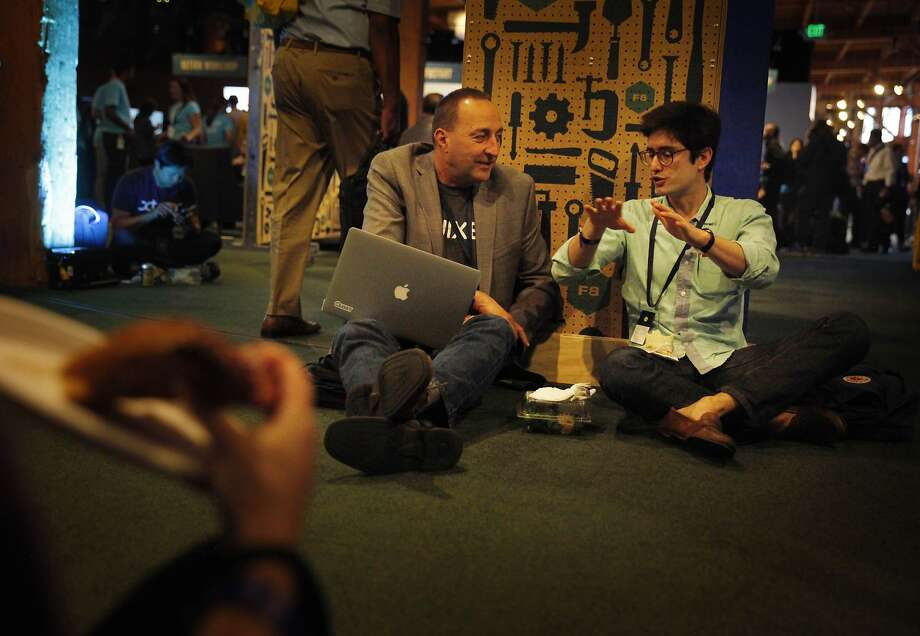 Joe Sandmeyer, Quixey technical sales engineer talks with Phillip Nelson, Quixey director of product as they sit on the floor while attending Facebook's F8 developers conference. Photo: Lea Suzuki, The Chronicle
