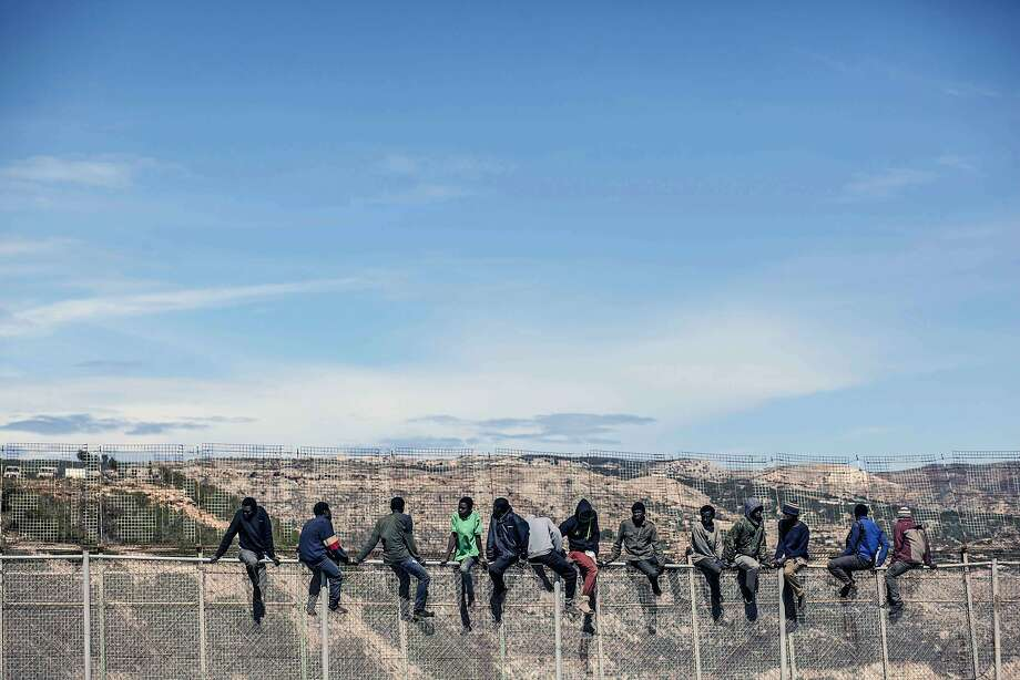Fence sitters: Would-be immigrants straddle a border fence separating Morocco from the 