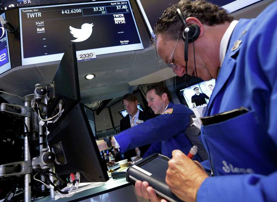 Trader Steven Kaplan, right, works at the post that handles Twitter, on the floor of the New York Stock Exchange, Wednesday, April 30, 2014.  Shares of Twitter dropped in morning trading Wednesday to their lowest point since the company went public in November. Investor concern remains over the short messaging service's ability to keep adding users and keep existing users engaged. (AP Photo) ORG XMIT: NYRD104 / AP