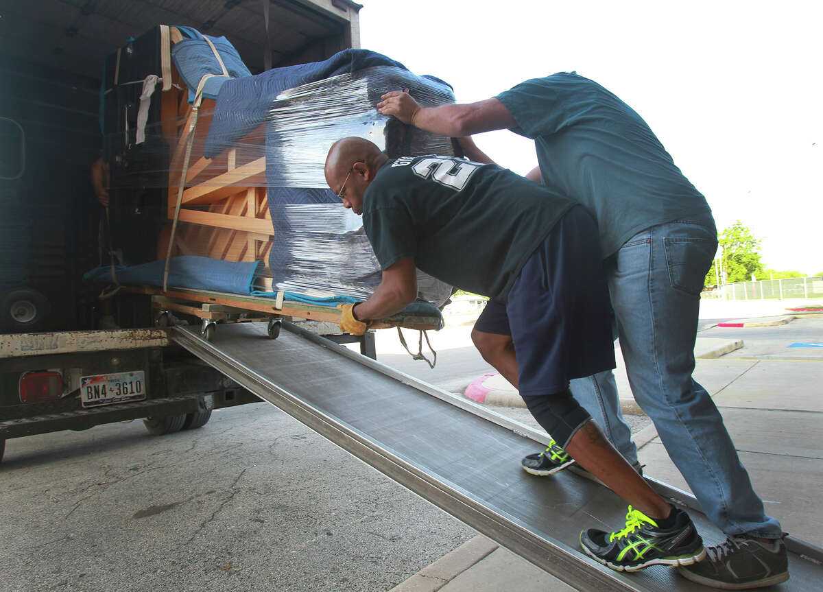 Michael Wilson (right) and Greg Blincoe (bald) move a new Steinway piano Wednesday April 30, 2014 out of a truck and into the Edgewood Theatre of Performing Arts. The instrument is a nine foot Model D concert grand piano and weighs 1,100 pounds.