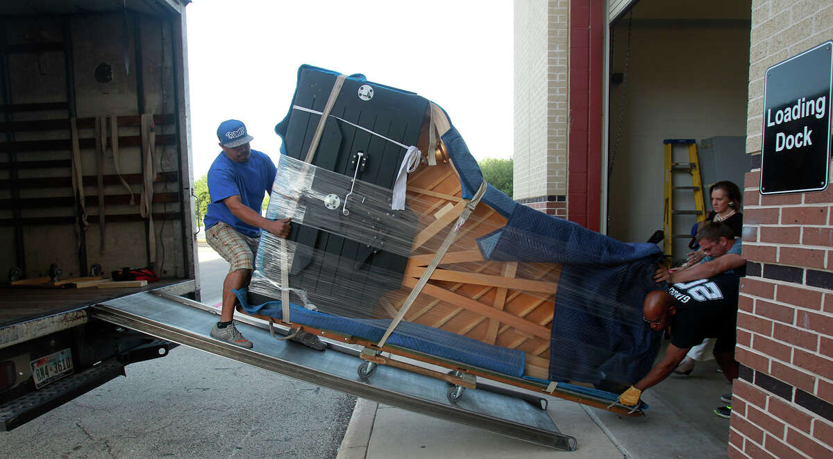 Michael Wilson (top, right) and Greg Blincoe (bald) move a new Steinway piano Wednesday April 30, 2014 out of a truck and into the Edgewood Theatre of Performing Arts. The instrument is a nine foot Model D concert grand piano and weighs 1,100 pounds. At the top of the ramp (left) is Mark Colon.