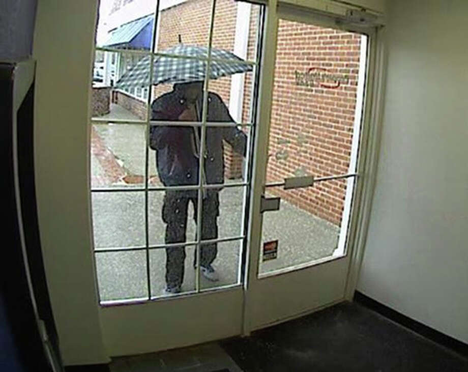 Darien police are asking anyone who may have seen a man, described as wearing a mask and blue hooded sweatshirt and carrying an umbrella, who is wanted in a robbery Wednesday afternoon at the People's United Bank in the Goodwives Shopping Center to call 203-662-5330. Photo: Contributed Photo, Contributed / Darien News