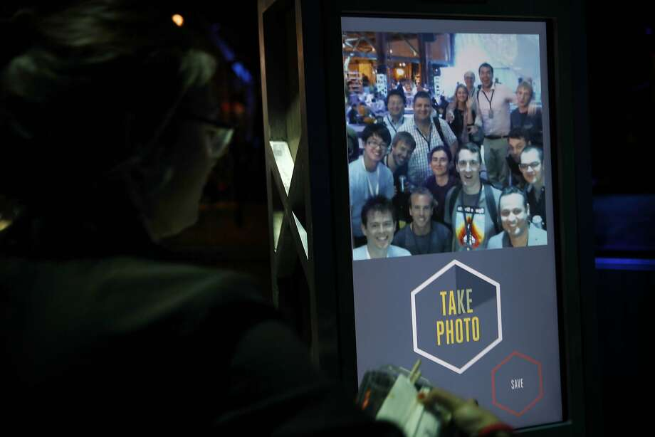 Elizabeth Gilmore, Facebook designer, presses a button to take a photo of F8 attendees gathered in front of a photo booth at Facebook's F8 developers conference . Photo: Lea Suzuki, The Chronicle