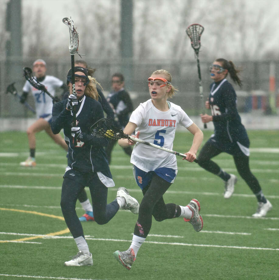 Danbury's Lindsey Eanniello, #5, brings the ball downfield against New Fairfield's Sara Bouwman, #8, during the New Fairfield at Danbury High School girls lacrosse game, in Danbury, Conn, on Wednesday, April 30, 2014. Photo: H John Voorhees III / The News-Times Freelance