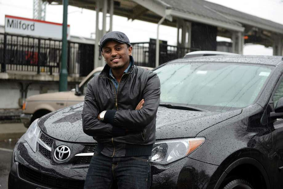 Yoseph Haile, a driver for the car service app, Uber, stands in front of his Toyota RAV4 Wednesday, April 30, 2014, at the Milford train station. Photo: Autumn Driscoll / Connecticut Post