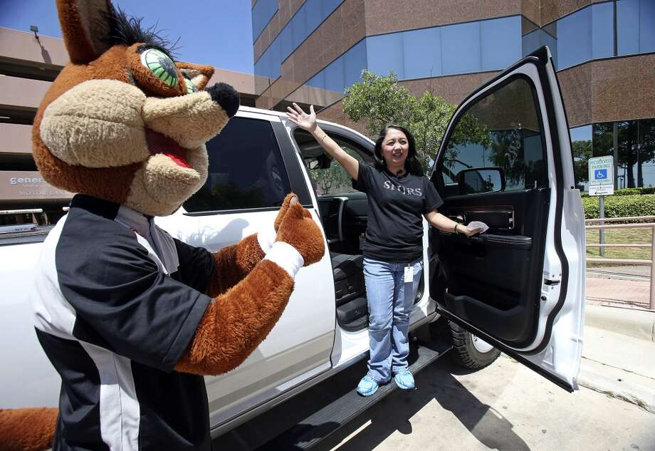 Coyote muses while Madyll Powao shows her winning raffle ticket as she takes delivery of the 2013 Ram 1500 Laramie, customized by Spurs forward Tim Duncan, on April 30, 2014.