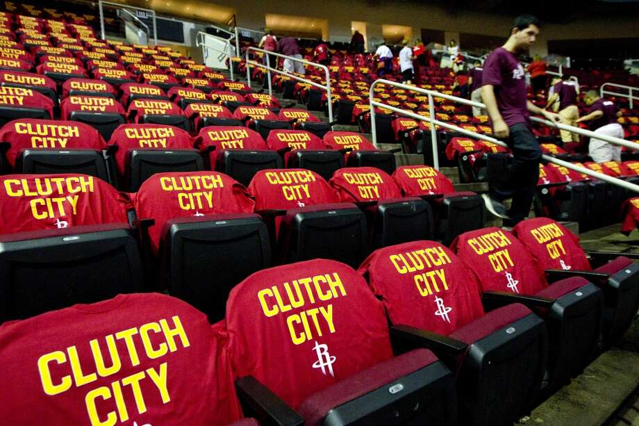 "Volunteers from Reagan High School place ""Clutch City"" t-shirts on the seats at Toyota Center before Game 5. Photo: Brett Coomer, Houston Chronicle"