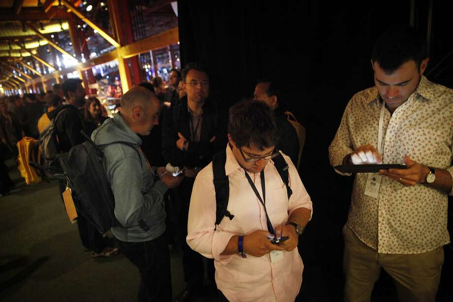 Will Ruben, left, and Adam Mosseri, Facebook product managers check their mobile devices as they stand at the front of the line for the opening keynote at Facebook's F8 developers conference. Photo: Lea Suzuki, The Chronicle