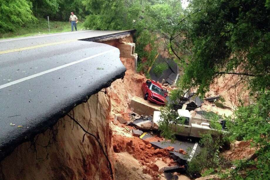 Vehicles rest at the bottom of a ravine after the Scenic Highway collapsed near Pensacola, Fla., Wednesday. Heavy rains and flooding have left people stranded in the Florida Panhandle and the Alabama coast. Photo: Katie E. King, MBO / Pensacola News Journal