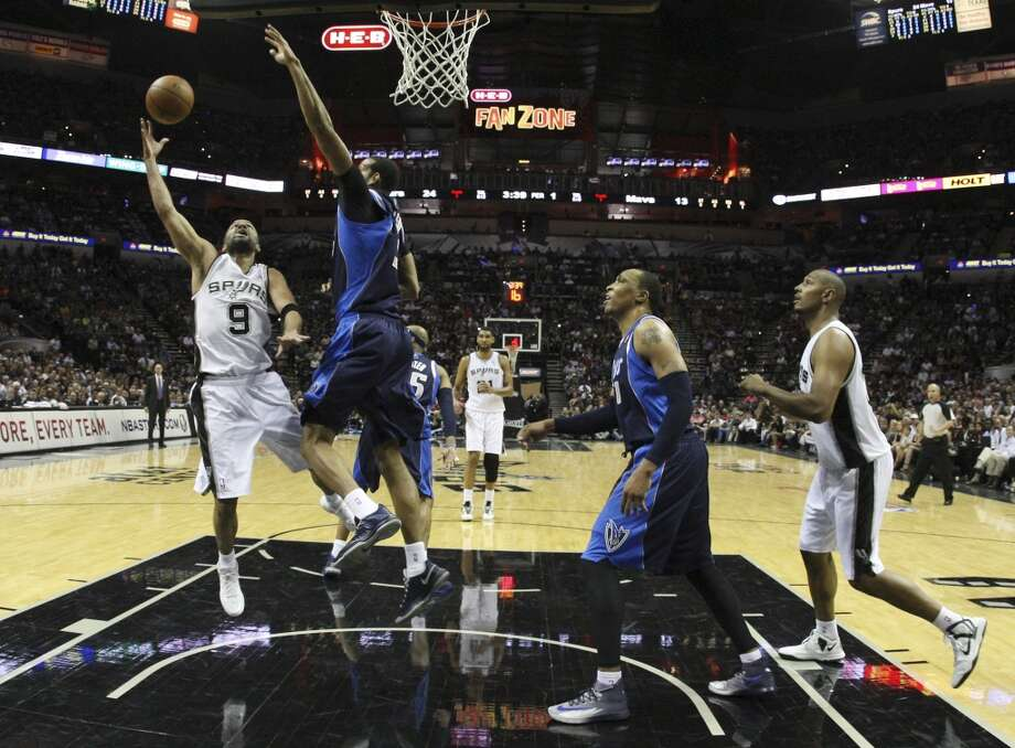 Spurs' Tony Parker (09) puts up a shot against Dallas Mavericks' Brandan Wright (34) in the first half of Game 5 of the first round of the Western Conference playoffs at the AT&T Center on Wednesday, Apr. 30, 2014. Photo: Kin Man Hui, San Antonio Express-News
