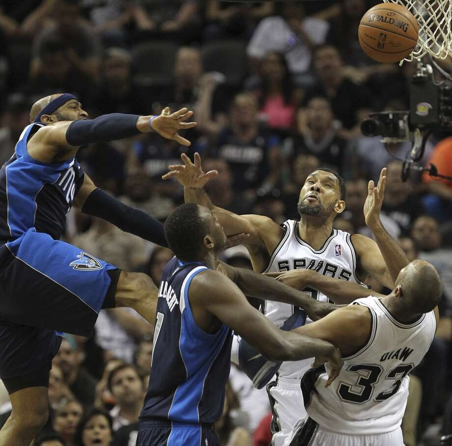 San Antonio Spurs' Tim Duncan goes for a rebound against Dallas Mavericks' Vince Carter, left, and Samuel Dalembert during the first half of game five in the first round of the Western Conference Playoffs at the AT&T Center, Wednesday, April 30, 2014. Photo: Jerry Lara, San Antonio Express-News