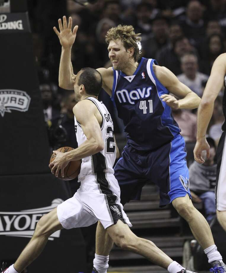 Spurs' Manu Ginobili (20) runs into the arm of Dallas Mavericks' Dirk Nowitzki (41) in the first half of Game 5 of the first round of the Western Conference playoffs at the AT&T Center on Wednesday, Apr. 30, 2014. Photo: Kin Man Hui, San Antonio Express-News