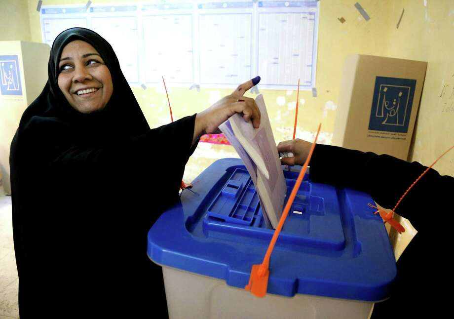 Despite tight security and the threat of violence, at least some Iraqis managed to show enthusiasm for Wednesday's parliamentary election. This woman cast her vote inside a polling station Baghdad. It was Iraq's  third parliamentary elections since the U.S.-led invasion that toppled dictator Saddam Hussein. Photo: Karim Kadim, STF / AP