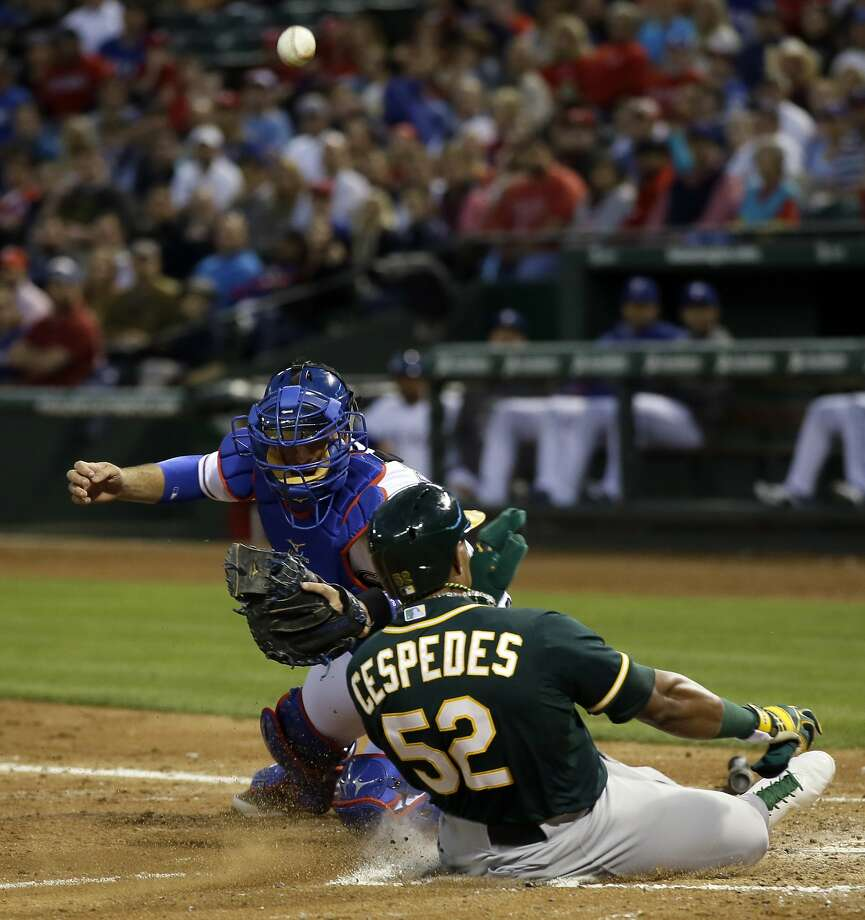 Oakland Athletics' Yoenis Cespedes (52) scores as Texas Rangers' J.P. Arencibia is unable to handle the throw to the plate in the fourth inning of a baseball game, Wednesday, April 30, 2014, in Arlington, Texas. (AP Photo/Tony Gutierrez) Photo: Tony Gutierrez, Associated Press