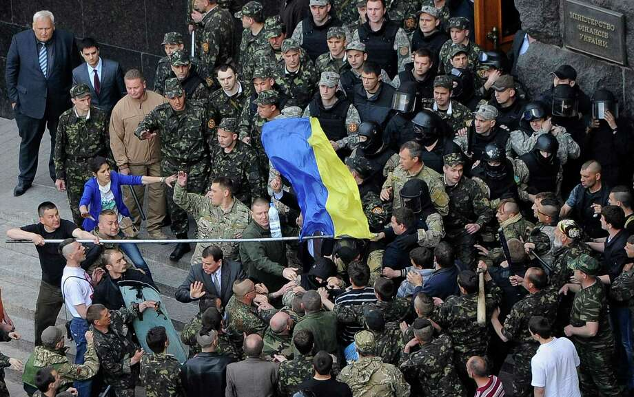 Members of Ukraine's State Security Administration, in uniforms, clash with the Euromaidan movement's self-defense units during a rally outside the Cabinet of Ministers in Kiev on Wednesday. As clashes continue, Oleksandr Turchinov, Ukraine's acting leader, said his country's forces have been brought to full readiness. Photo: POOL / X80003