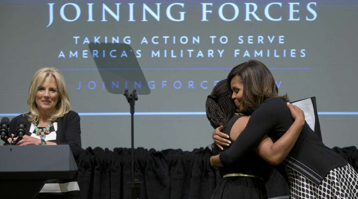 First lady Michelle Obama hugs Chrissandra Jackson as Jill Biden looks on at an event marking the third anniversary of the Joining Forces program.