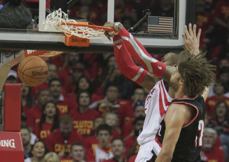 Rockets center Dwight Howard dunks as Trail Blazers center Robin Lopez looks on. Photo: James Nielsen, Houston Chronicle