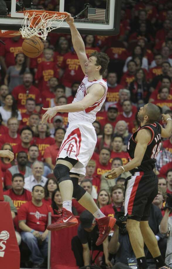 Rockets center Omer Asik dunks as Trail Blazers forward Nicolas Batum looks on. Photo: James Nielsen, Houston Chronicle