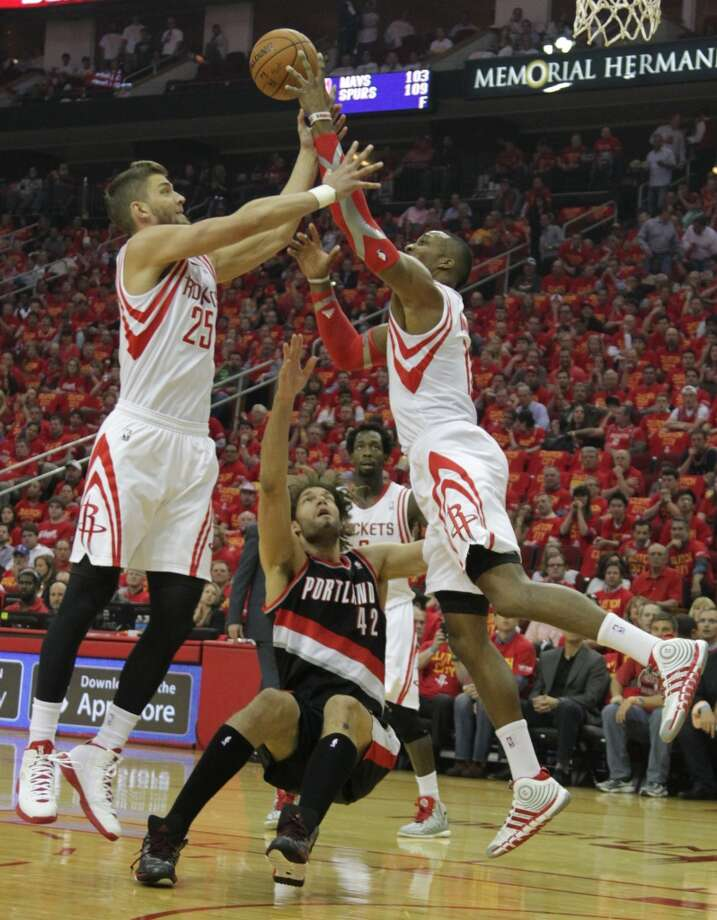 Rockets forward Chandler Parsons left, and Rockets center Dwight Howard right, beat Trail Blazers center Robin Lopez to a rebound. Photo: James Nielsen, Houston Chronicle