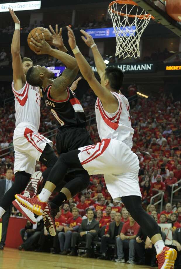 Rockets forward Chandler Parsons left, and Rockets guard Jeremy Lin right, double-team Trail Blazers guard Damian Lillard. Photo: James Nielsen, Houston Chronicle
