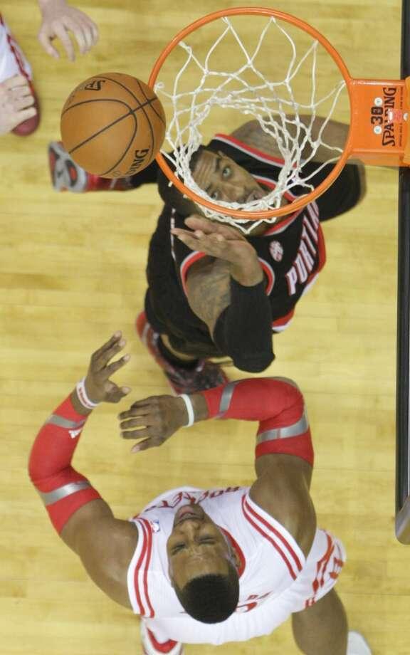 Trail Blazers forward LaMarcus Aldridge watches his shot fall as Rockets center Dwight Howard looks on. Photo: James Nielsen, Houston Chronicle