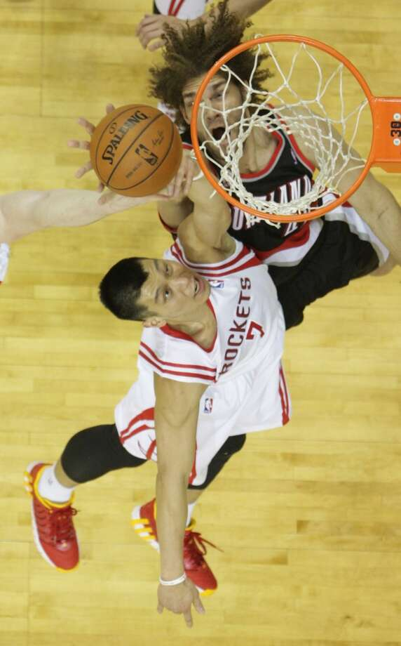 Rockets guard Jeremy Lin and Trail Blazers center Robin Lopez jump for a rebound. Photo: James Nielsen, Houston Chronicle