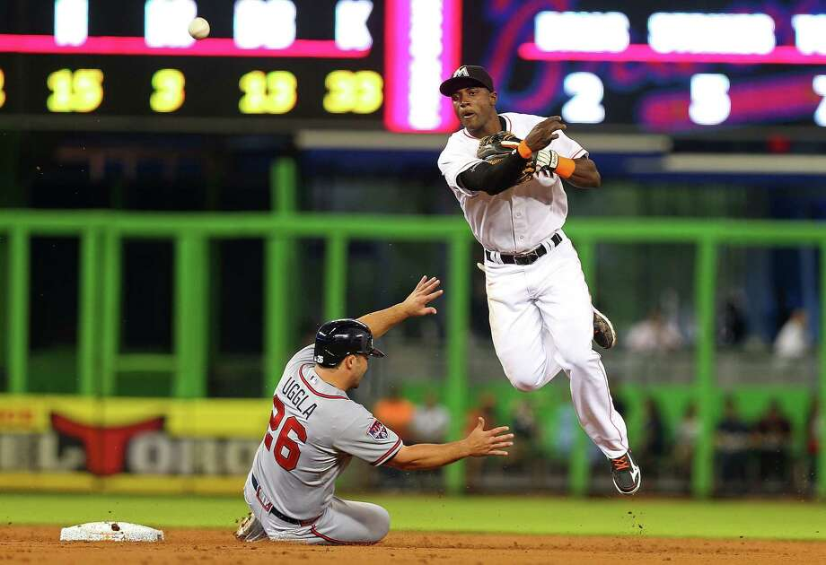 MIAMI, FL - APRIL 30:  Adeiny Hechavarria #3 of the Miami Marlins makes a throw to first as Dan Uggla #26 of the Atlanta Braves slides into second during a game  at Marlins Park on April 30, 2014 in Miami, Florida.  (Photo by Mike Ehrmann/Getty Images) ORG XMIT: 477582691 Photo: Mike Ehrmann / 2014 Getty Images
