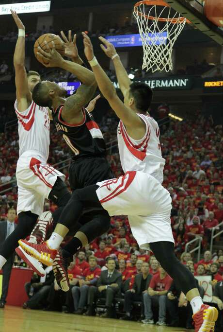 The Rockets' Chandler Parsons left, and Jeremy Lin squeeze the Trail Blazers' Damian Lillard. Photo: James Nielsen, Staff / © 2014  Houston Chronicle