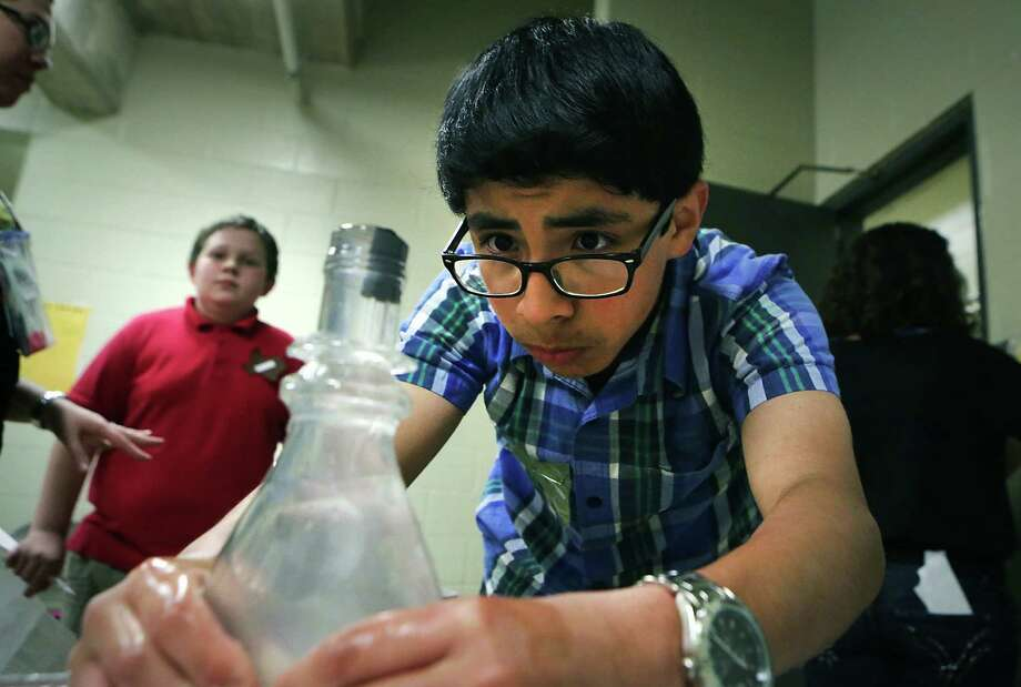 Otilio Ramirez squeezes a bottle filled with water, watching closely to see if the bobber inside goes down, at the Bobber in a Bottle station. Middle school students in the NISD are participating in the district's 31st Gifted Program's Mentathlon. Photo: Photos By Bob Owen / San Antonio Express-News / © 2012 San Antonio Express-News
