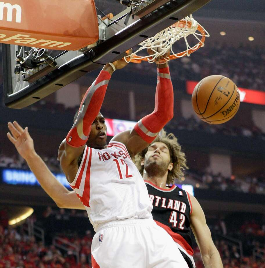 The Rockets' Dwight Howard dunks in front of the Trail Blazers' Robin Lopez. Photo: Bob Levey, Getty Images