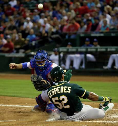 Yoenis Cespedes adds to the onslaught in the A's 12-1 win as a throw eludes Rangers catcher J.P. Arencibia. Photo: Tony Gutierrez, STF / AP