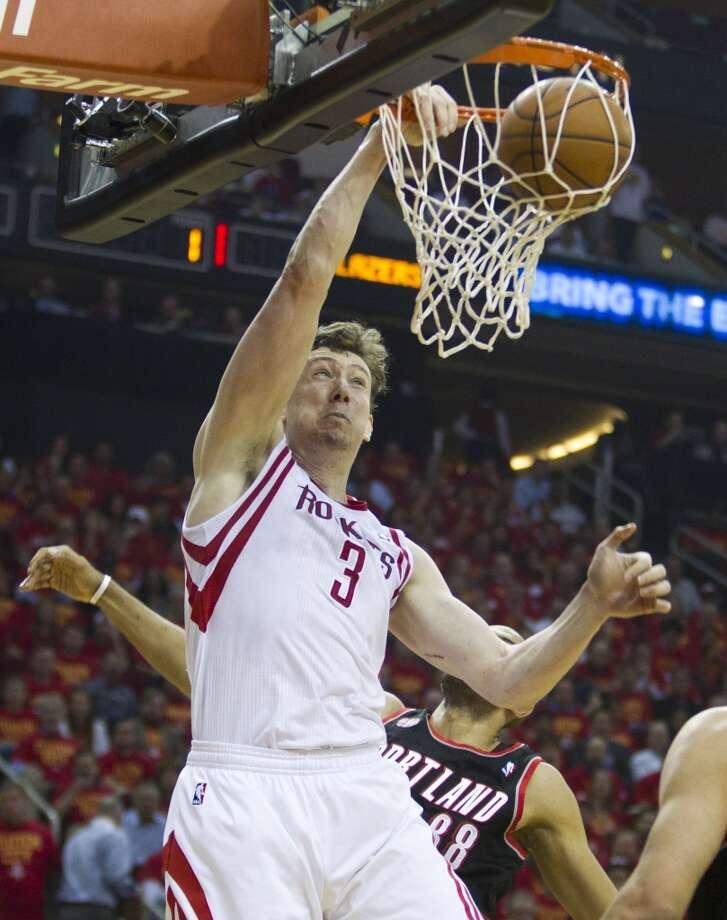 Rockets center Omer Asik dunks against Trail Blazers forward Nicolas Batum. Photo: Brett Coomer, Houston Chronicle