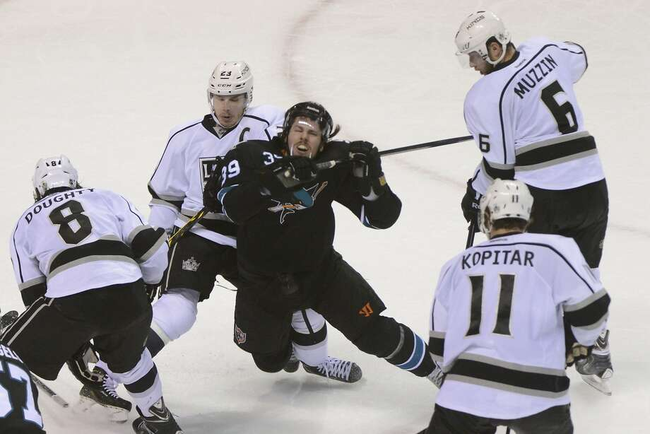 Los Angeles Kings right wing Dustin Brown (23) checks San Jose Sharks center Logan Couture (39) during the second period in game seven of the first round of the 2014 Stanley Cup Playoffs at SAP Center at San Jose. Photo: Kyle Terada, Reuters