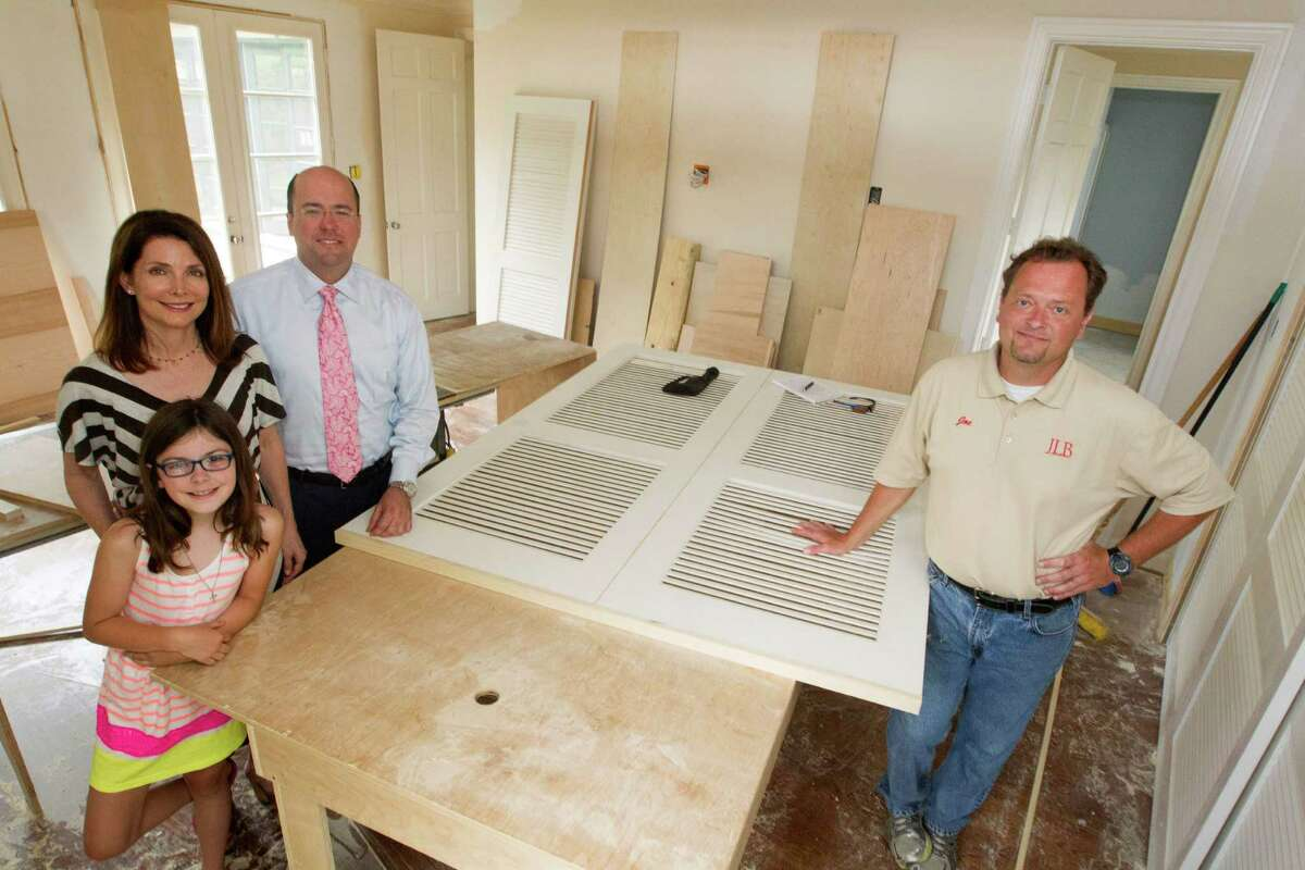 Katherine DeLaune and Lee Steely along their daughter Ava, 9, pose for a portrait with their builder Joe Bielamowiez, right, on Monday, April 21, 2014, in Houston. Their upper Kirby home is going through a major renovation. ( J. Patric Schneider / For the Chronicle )