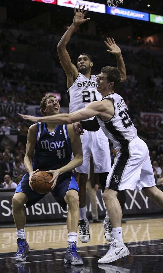 San Antonio Spurs' Tiago Splitter and Tim Duncan surround Dallas Mavericks' Dirk Nowitzki during the second half of game five in the first round of the Western Conference Playoffs at the AT&T Center, Wednesday, April 30, 2014. The Spurs won 109-103 to lead the series, 3-2. Photo: San Antonio Express-News